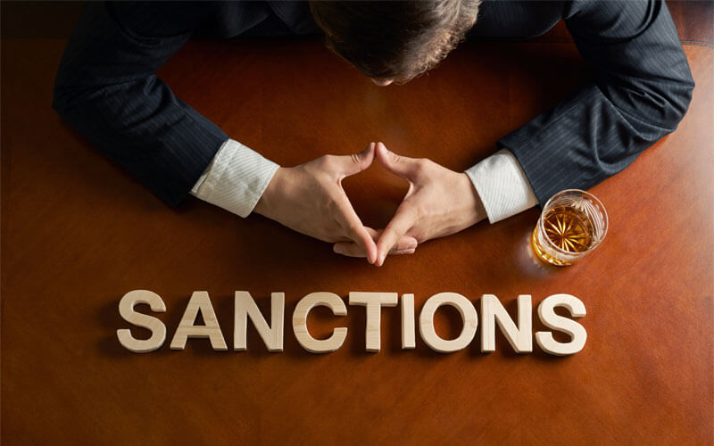 Sanctions-Written-on-Desk