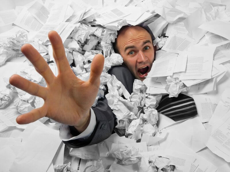 Businessman-Sinking-In-Heap-Of-Paperwork